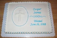 Half sheet cake with buttercream frosting. Shell oval border with white chocolate cross mold inside. Scroll work from pattern press. Shell border with dots for top and bottom borders.
