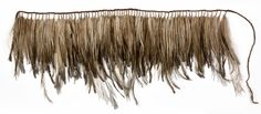 A short apron made from brown emu feathers and fibre. One hundred and twenty nine small bunches of feathers are held together at their quill ends with fibre and then wrapped around a fibre suspension cord. The bunches are placed centrally - the outer ends of the cord form ties.