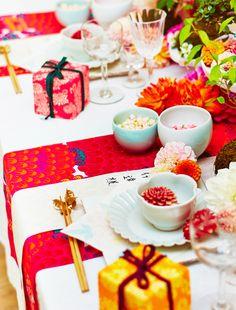和のテーブル装花や装飾はいかがでしょう。 テーブル中央から手前に流すように手ぬぐいをセット。手拭いの幅の1/3程度に細長くカットした和紙を重ねて、ショープレートのセッティングの下に敷きます。和紙にはゲストの名前を入れて、粋な席札として利用。