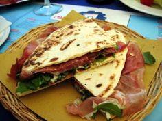 De piadina, komt oorspronkelijk uit de regio Emilia-Romagna. Het is een plat gebakken brood dat warm wordt gegeten met vleeswaren, kaas en salade. Ingrediënten voor 10 broodjes: 500 gram bloem 75 ml olijfolie 3 theelepels zout 2 theelepels bakpoeder 5...