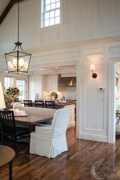 Fabulous white country kitchen | clerestory window | beadboard | beautiful mouldings | cool lantern over the table | slip covered dining chair | wall sconces | mismatched chairs