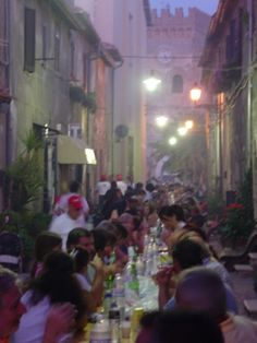 Italian architecture, good food & drink on long tables under dreamy lights: does it get much better than this? Image from the book, Beyond the Pasta: Recipes, Language & Life with an Italian Family, by Mark Leslie