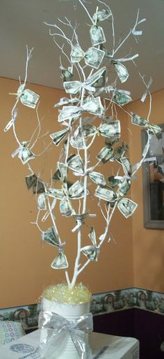 Use the easter branches for hte tree, put them into a terra cotta pot with some potting soil. Use ribbon to attach the money to the tree. Wrap the pot in a pretty blue and gold ribbon with a bow.