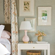 The master bedroom is calm and a relaxing with a seaglass colored grass cloth from Rose Tarlow Melrose House on the walls, pale pink lamps on white nightstands and botanical print artwork.