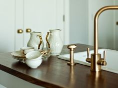 Modern kitchen with brass fixtures and wood countertops by WORKSTEAD