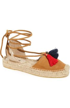 Boldly hued tassels add boho flair to this trendy lace-up sandal set atop a woven platform.
