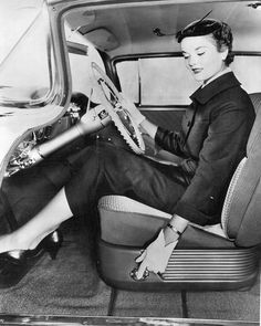 Model demonstrating seat controls on a 1955 Oldsmobile.