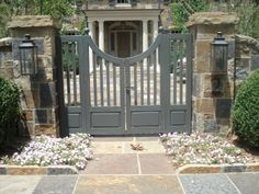wooden gates with a weathered paint finish flanked by large boxwood
