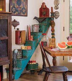 Primitivas no jogo - Stairway to Heaven A cozinha dispõe de uma escada para o céu-antiguidades céu, que é! Um conjunto de velhas escadas azuis culminou com latas vintage e outros colecionáveis empresta estilo arquitetônico colorido para o quarto. Julie variou as alturas e materiais das peças-de caixas de chá e uma estatueta de corvo para moinhos de vento em miniatura e estanho chifres, a fim de maximizar o interesse. Achados peculiares, incluindo um distribuidor de chicletes vermelho e um…