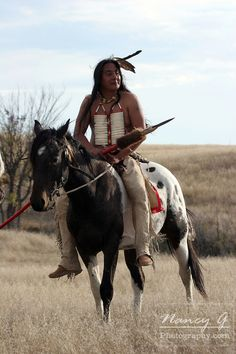 A Native American on horseback in South Dakota with a eagle feather in his hair. Nancy Greifenhagen Photography