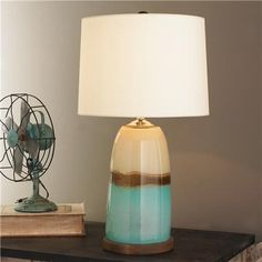"""Strata Art Glass Table Lamp Earth, sea and clouds seem to unite in this brown, aqua, and cream art glass table lamp. Translucent parchment paper shade complements the creamy dappled glass.3-way 100 watts. (25""""Hx14""""W) 8' clear silver cord. 7.5"""" stained wood base. Switch on socket. Product SKU: TL14015 AQ Price: $299.00; shadesoflight.com"""