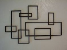Modernistic metal wall sculpture with bold eye appeal. A mid century De Stijl styled piece that features a dimensional abstract geometric design