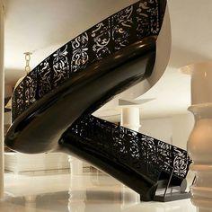 Escada helicoidal com guarda corpo todo trabalhado em ferro preto.