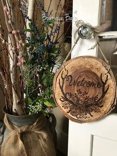 Welcome/Wood Sign/Antlers/Woodburned Art/Birch/Lake House Decor/Cabin Decor/farmhouse decor/Rustic Decor/Handmade Gift/Housewarming Gift Welcome Sign A rustic wood sign to welcome your friends and family to your home! A pretty collection of flowers entwining deer antlers is wood burned