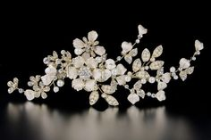 A sophisticated bridal clip of matte silver flowers, rhinestone jewels, pearl encrusted leaves and floating pearls. On an alligator style pinch clip. Length de