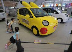 Crianças olha carro Porte, da Toyota, decorado com motivo da série de anime Pokémon em showroom da marca.