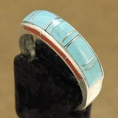 Inlaid Turquoise  Spiny Oyster Sterling Silver Ladies Ring  This Inlaid Turquoise Ring is a beautiful and traditional piece of hand made southwestern Turquoise jewelry. This Turquoise Inlaid Ring features an masterfully hand made inlaid design made with hand cut stones of genuine Turquoise and Spiny Oyster. The Turquoise  Spiny Oyster have been set against the brilliance of shimmering Sterling Silver. This Sterling Silver Inlaid Ring is 1/4 wide.  Stamped Sterling.
