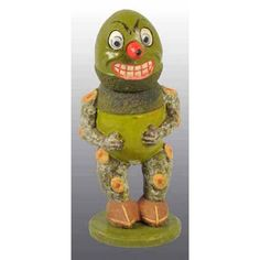 German Halloween Acorn Veggie Man Candy Container. Painted composition Figure with acorn shaped head and mechanical nose. Body with oak branch arm and legs on acorn feet.