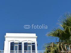 Weiße Villa mit Palmen vor blauem Himmel an der Hafenpromenade in Bodrum in der Türkei