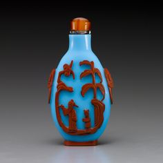 A finely carved red-overlay glass bottle carved with blossoming prunus trees and birds and a finely carved cameo agate snuff bottle, cleverly carved utilizing the darker brown markings with a badger seated on rockwork.