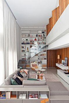 O espírito dos lofts nova-iorquinos está presente neste apartamento de 130 m². Tudo graças ao projeto do escritório Rocco, Vidal + Arquitetos, que redistribuiu e personalizou os espaços. A estante de laca tem a altura do pé-direito duplo e fica no canto