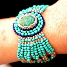 Turquoise cuff features an Eilat stone, and tiny glass beads. It features a dainty magnetic clasp.