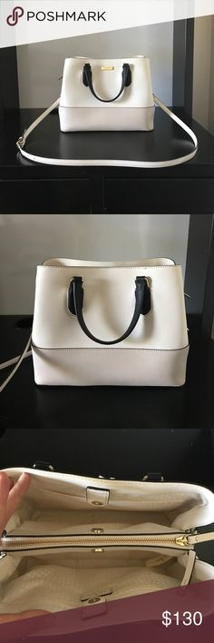 Kate Spade Bag Authentic Kate Spade bag. White and tan color block with black handles and trim and both gold and silver hard ware! Clean for a white bag. Only a couple small marks on the inside. Outside is still clean! The back side only has extremely slight coloring from rubbing against closed (pictured, as you can tell it's almost unnoticeable. Only actual sign is marks on bottom from setting on the ground. kate spade Accessories