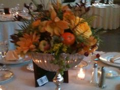 Venue: Knowlton mansion November Harvest silver tall urn like base filled with dahlia's,orchids,roses,copper beach leaves,china berries green, rose hips,kangaroo paw,solidago, genestra, added baby lady fingers apples and small clementines and  Kumquats.....so cute!!, but still elegant