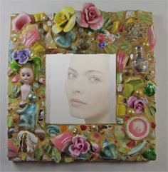 """Doll Face 10"""" Mirror of antique china shards, Capodimonte flowers, vintage jewelry, and an old doll."""