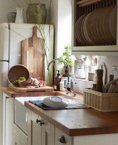 Et kjøkken i landlig stil med benkeplater i tre, kremhvite skap og åpen oppbevaring.