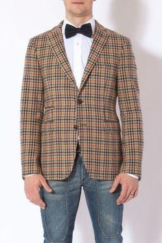 <p>Giacca beige, con linee verticali e orizzontali, rosso, verde, nero, bianco e bruno</p>