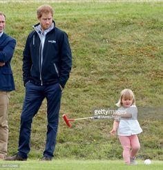 Prince Harry looks on as Mia Tindall swings a polo mallet as they attend the Maserati Royal Charity Polo Trophy Match on June 18, 2016 in Tetbury, England.