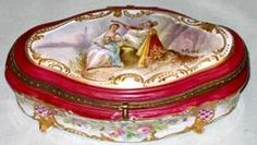 """Year: 1875 - 1900 A French Sevres Porcelain jewelry box having an oval shape with molded feet, the body painted outside and inside with floral bouquets, the metal mounted hinged lid painted with courting couple in a landscape signed """"P. Roche"""", circa 19th century."""