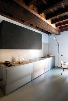 Dans la cuisine, lampe Jean Prouvé pour Vitra. Plafond bois brut foncé