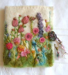 . . Garden of Delight Needle Case. Each book is something totally unique and incredibly beautiful. Tiny stitches, stump work, beads and a button adorn each book. ~By Jill Verbick, Fiberluscious