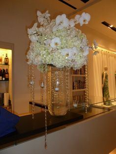 Bar Arrangement... white hydrangeas and orchids... accented by hanging crystals and votive candles.
