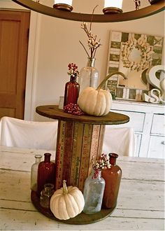 DIY:  Wooden spool is given a facelift using vintage yard sticks!  Inspiration.