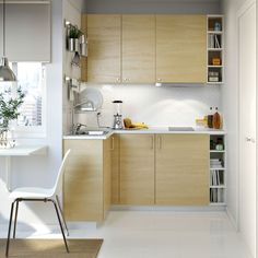 A small white kitchen with birch doors and white worktops. Combined with stainless steel handles.