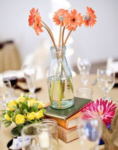 Orange or white daisies in turquoise vase on top of boy books for centerpieces