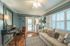 Tropical Living Room with flush light, Ceiling fan, terracotta tile floors, High ceiling, Carpet, Crown molding