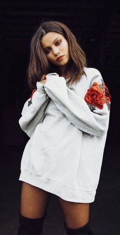 I'm not sure if this is a sweatshirt or a sweater, doesn't matter. I like that its oversized and the rose appliqué on the shoulder is beautiful. She has on thigh high black boots. It's a bold cool look.