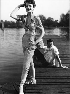 Pat Goddard wearing a Malcolm Brown gingham blouse and jeans posing with Roger Moore, 1952. photo by John French