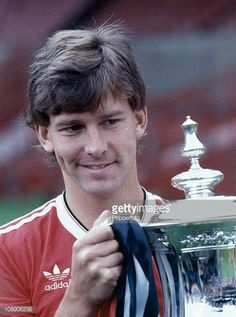 Manchester United captain Bryan Robson holding the FA Cup at Old Trafford Manchester in August 1983