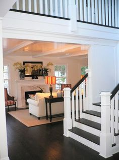 Nice living room layout and classic stairs to a loft style hallway. Love the dark wood and crisp white combo.