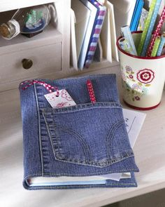 Hübschen Sie ein einfaches Buch mit einem Umschlag aus einer ausrangierten Jeans auf. Der Clou: Die Hosentasche.