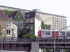 Hamburg Eimsbüttel Hoheluft (P7270071 U-Bahnbrücke Hoheluft - ein Hochbahnzug fährt in den Bahnhof ein - im Hintergrund ein Hochhaus am Grindelberg.)