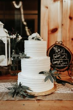 Classic three-tier white wedding cake with simple greenery accents | Image by Gloria Goode Photography