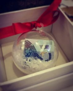Perfect homemade Christmas gift idea. Very easy to make. Coinage into a clear bauble  (you can buy them from any craft store) add some synthetic snow stuff . Tie with a festive coloured ribbon. Placed in an old watch box. Perfect gift for Christmas . Alternative ways to gift for Christmas
