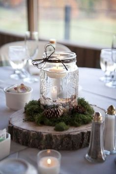 DIY winter wedding centerpiece: floating tealight candle, mason jar, pinecones, on a tree slice - rustic winter wedding inspiration - our centerpieces, photographed by Bri Herrman Wedding Centerpieces Mason Jars, Winter Wedding Centerpieces, Rustic Centerpieces, Shower Centerpieces, Banquet Centerpieces, Floating Candle Centerpieces, Mason Jars For Weddings, Wedding Mason Jars, Rustic Centerpiece Wedding