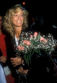 Farrah smiles, holding a bouquet of roses.
